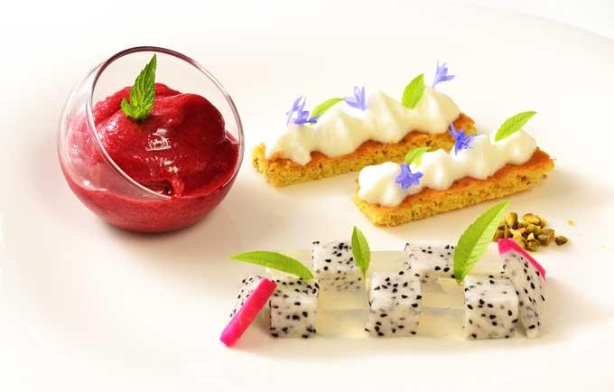 Dessert mit Kirschsorbet, Pistaziensablé, Verbenenschaum, Birkensaft-Drachenfrucht Mosaik, auf dem Teller angerichtet