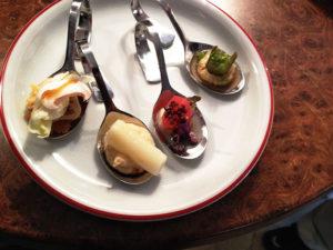 vier angerichtete Löffelgerichte auf Teller