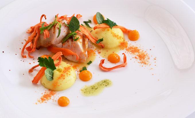 Kaninchen angerichtet auf Teller mit Karotte, Aprikose, Kartoffel