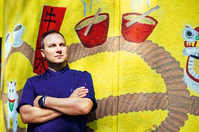 Portrait Tim Raue vor Graffiti Wand stehend